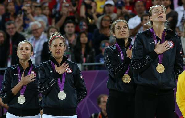 Gold medalist Kerri Walsh Jennings, right, weeps as she sings the U.S. national anthem, while teammate Misty May-Treanor and silver medalists April Ross and Jennifer Kessy, far left, join in during the medal ceremony for women's beach volleyball.