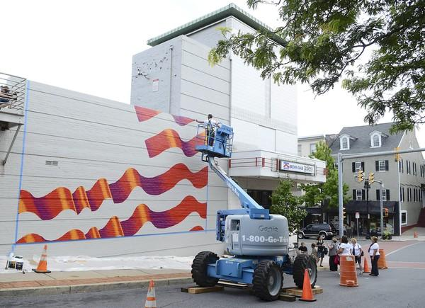 Artist Scott LoBaido of Staten Island paints an American flag on the west side of the State Theater on Wednesday.