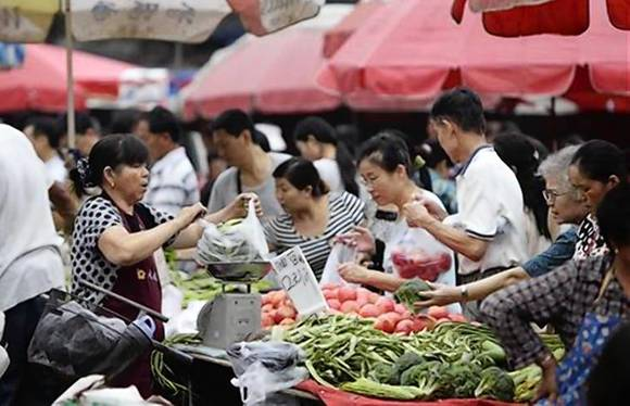 Customers buy vegetables at a market in central Beijing