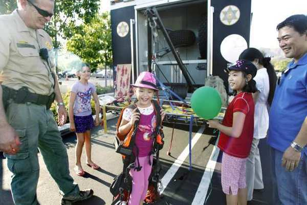 Angelica Aniciete, center, tries on a vest during National Night Out in La Canada on Tuesday.