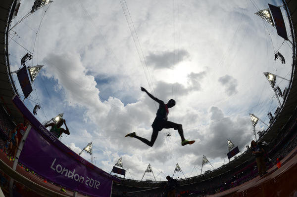 An athlete competes in a men's 3000m steeplechase heat as viewed through a fisheye lens.
