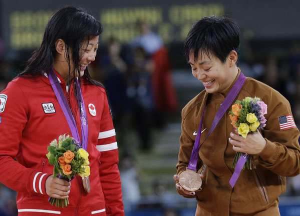 Bronze medalist Carol Huynh of Canada, left, and bronze medalist Clarissa Chun of the United States, participate in the awards ceremony Wednesday at the Olympic Games in London.