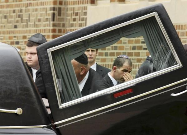 A pallbearer reacts after placing the casket of Dr. Donald Liu into a hearse Wednesday at KAM Isaiah Israel Congregation. Liu died Sunday after rescuing two children from Lake Michigan.