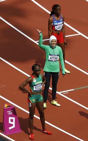 Saudi Arabia's Sarah Attar, center, waves to a cheering crowd before competing in an 800-meter heat against Grenada's Neisha Bernard-Thomas, bottom, and Colombia's Rosibel Garcia on Wednesday.