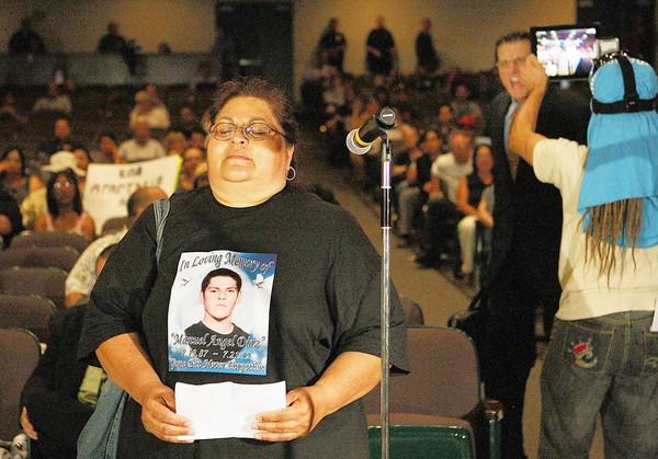 "An irate man shouts insults at Genevieve Huizar, the mother of Manuel Angel Diaz, who was killed by Anaheim police. Before the outburst, she told the council: ""I want young children to have hope, have peace."""