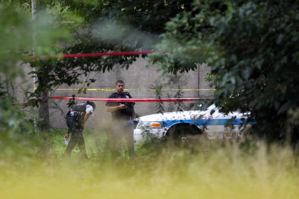 Chicago Police wait at 78th Street and Lowe Avenue where a woman's body was found.