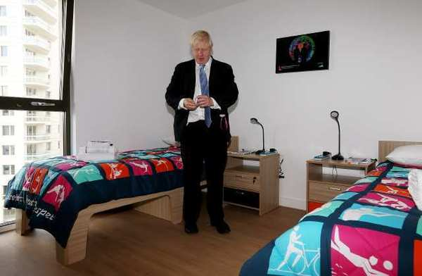 London Mayor Boris Johnson picks up a packet of Olympic-branded condoms during a visit to the Olympic Village on July 12.