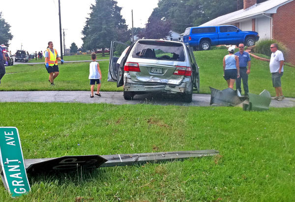 The driver of this Honda minivan was taken to Meritus Medical Center after a two-vehicle collision Thursday at the intersection of Sharpsburg Pike (Md. 65) and Grant Avenue. The minivan was pushed into a stop sign (in foreground), knocking it over.