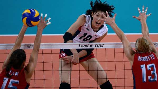 South Korea's Kim Yeon-Koung spikes past Christa Harmotto, right,  and Logan Tom of the U.S.