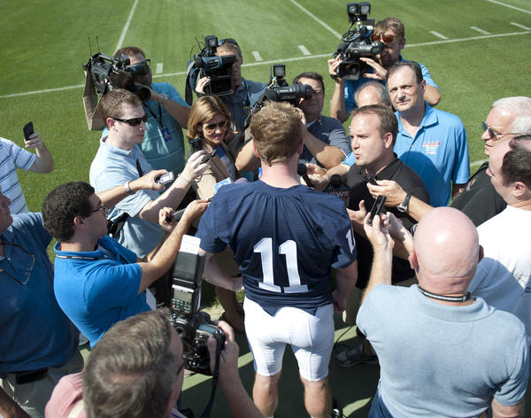 Penn State football holds is annual media day at Beaver Stadium in University Park. Here, Penn State Nittany Lions quarterback Matthew McGloin (11) is surrounded by reporters.
