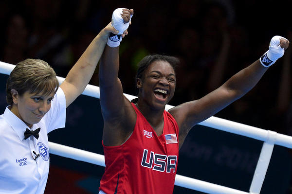 U.S. boxer, Claressa Shields, right, also known as T-Rex, celebrates becoming the first Women's Middleweight Olympic gold medalist, overtaking Russia's Nadezda Torlopova at the London Olympic Games.