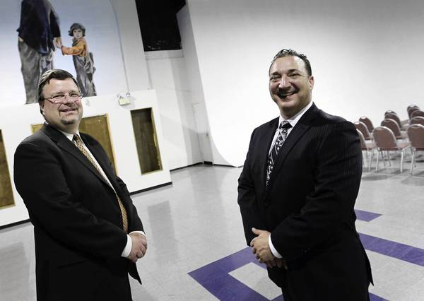 St. Augustine College President Andrew Sund, left, and project developer Gary Keller in a building slated for remodeling in the Essanay Studios complex. Charlie Chaplin and Jackie Coogan are portrayed on the wall at rear.