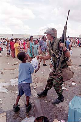 <b>Not to be overlooked</b><br>Spc. Michael Cleary gives a bag of ice to a boy who was overlooked in a Homestead ice line.