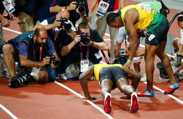 Photographers take pictures of Jamaica's Usain Bolt (bottom) doing push ups as he celebrates next to second place finisher Jamaica's Yohan Blake after winning the men's 200m final at the London 2012 Olympic Games at the Olympic Stadium August 9, 2012.