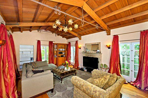 The living room of the Carthay neighborhood house features vaulted wood ceilings and a fireplace.