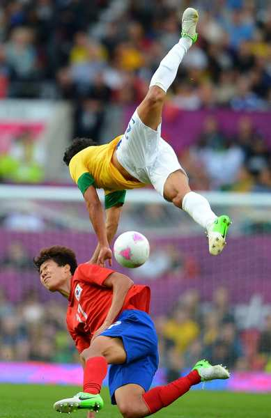South Korea's Kim Hyunsung, below, collides hard with Brazil's Rafael Pereira Da Silva as they compete for a 50-50 ball during their semifinal match at the London 2012 Olympic Games.