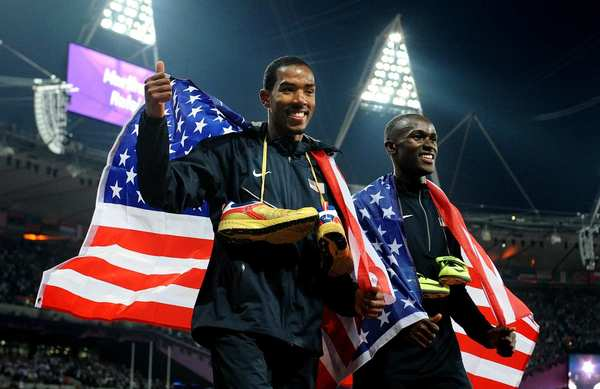 Triple jump gold medal winner Christian Taylor, left, and silver medal winner Will Claye, both of the United States, carry the American flag after their competition Thursday.