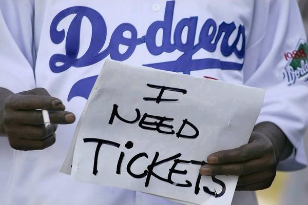 A scalper outside Dodger Stadium — one of the venues listed in the proposed injunction — holds a sign indicating that he has tickets to sell to potential buyers.