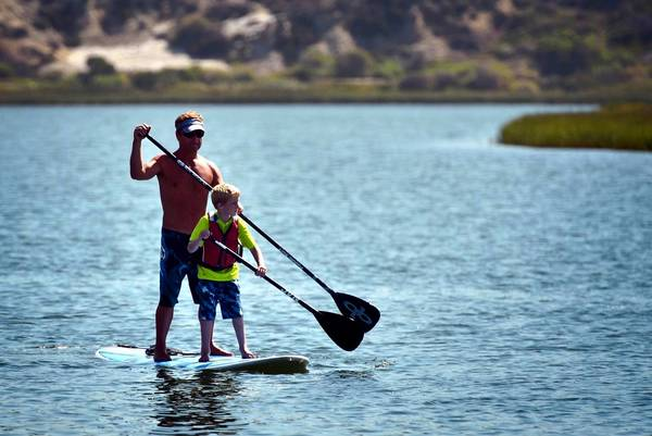 Gavin Montelone, 6, who has cystic fibrosis, paddles down Upper Newport Bay on Thursday with the help of volunteer Darren Delmonico as part of a Miracles for Kids day camp.