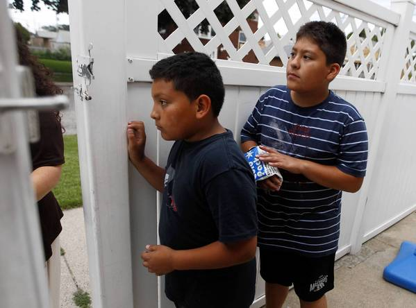 Andres Limias Villa, 9, left, and Omar Limias Villa, 11, peer out their front gate after seeing Chicago police cars swarm outside their West Lawn home. The officers detained one person and were searching the street for a possible gun he had thrown.
