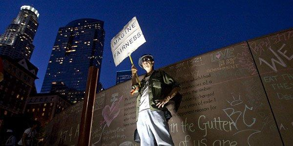 "Brian Connolly of Occupy Los Angeles holds a sign by a wall with ""chalk art"" as Occupy L.A. members and supporters protest at Pershing Square, a few blocks from downtown's Art Walk."