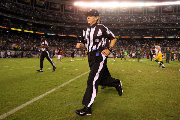 NFL referee Shannon Eastin jogs off the field after becoming the first female to ever officiate an NFL game.
