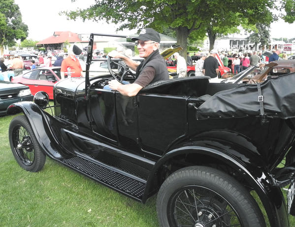 Frank Holzschu, of Petoskey, sits behind the wheel of his 1926 Ford Model T at the Harbor Springs Car Festival, Thursday evening. The event, hosted in Harbor Springs' Zorn Park, features cars of all types and draws a large crowd of spectators.