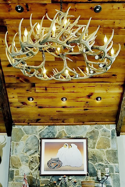 An antler chandelier hangs above a mantle in the farmhouse at Knob Hall.