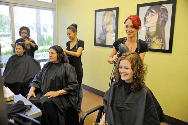 Aveda Institute stylists, from left,) Natachia Louis, Francy Sarmiento and Lacy Neugebauer work on customers Tracee Gibson, Courtney Silverman and Aoife Charles.