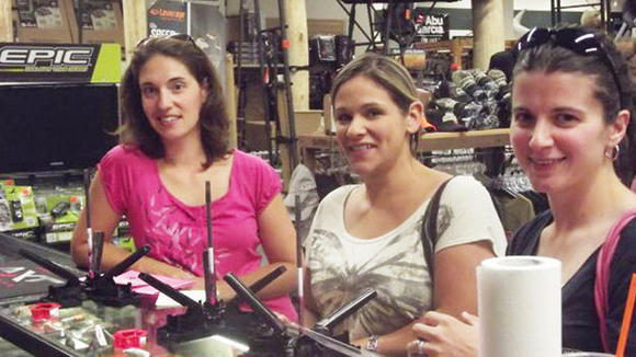 Mandy LaBarge, Carmen Schaub and Megan Polhemus (l-r) learn how to fletch an arrow by adding fins to a custom arrow ink pen.
