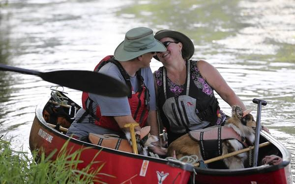 John Anderson, left, and his partner Sherri Graham, kiss in their canoes before heading down the river in Joliet, Saturday Aug, 4, 2012.  They met several years ago canoeing, but discovered love last year.