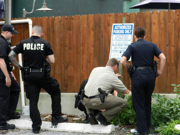 Police search weeds near a parking area at 24 1/2 W. Franklin St. in Hagerstown for evidence in connection with a shooting incident Friday. A 3-year-old boy found a handgun at that location and accidentally shot himself, police said.