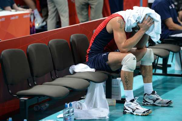 Donald Suxho of the U.S. sits alone after losing a quarterfinal match to Italy. The U.S. team was knocked out of the men's indoor volleyball tournament.