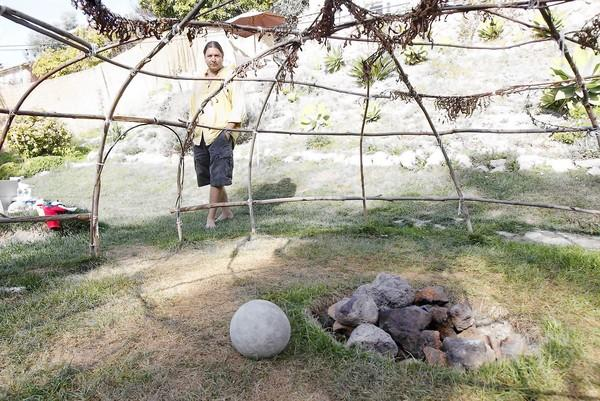Andrew Soliz stands with his backyard sweat lodge in Bluebird Canyon.