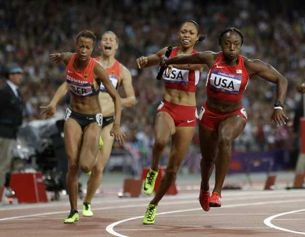 Bianca Knight, right, takes the baton from U.S. teammate Allyson Felix in the women's 400-meter relay final.