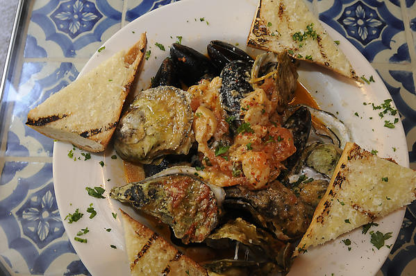Seafood Provencal consists of steamed Wellfleet oysters, littleneck clams, P.E.I. mussels, plum tomato, garlic cloves and white wine.
