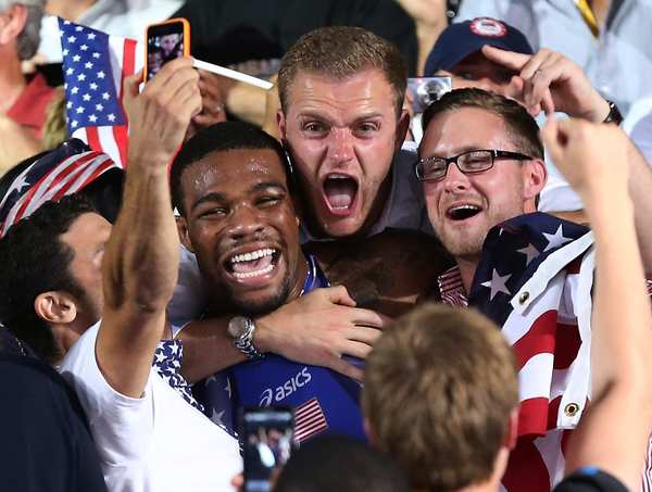 Jordan Burroughs of the United States celebrates with fans in the stands after beating Iran's Sadegh Saeed Goudarzi  to win the men's  freestyle wrestling gold medal.