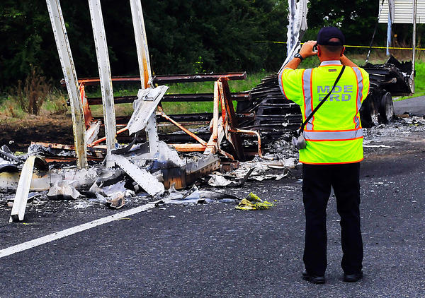 An investigator with the maryland Department of the Environment photographs burned-out trailer Friday on east-bound Interstate 70 west of Clear Spring Friday afternoon. The trailer caught fire and was believed to be carrying a blasting agent.