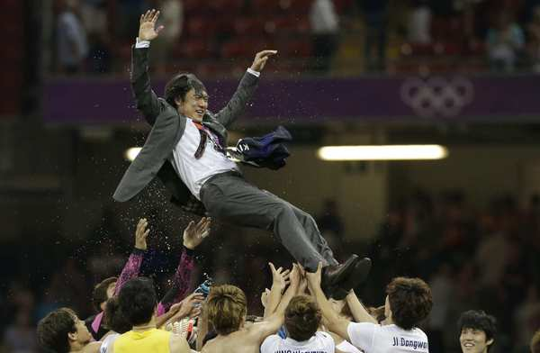 South Korea's soccer team tosses head coach Hong Myung-bo  after the team won the  men's soccer bronze medal match against Japan.