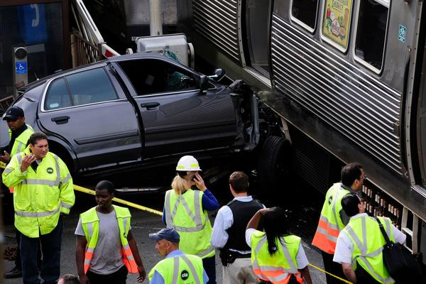 Rescue personnel work at the scene of a crash involving an unmarked Chicago police car and a CTA Brown Line train at the Kedzie station.