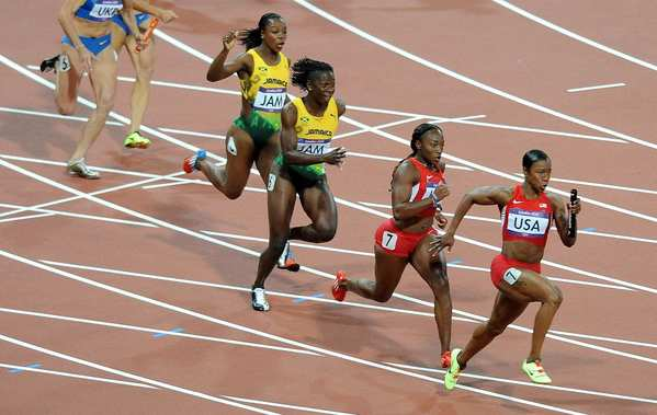 Carmelita Jeter of the United States takes the baton from Bianca Knight on the last leg of the 4x100 relay race.