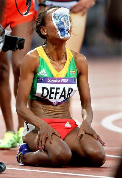 Ethiopia's Meseret Defar puts a picture of the Virgin Mary on her face after winning the gold medal in the 5,000 meters race.