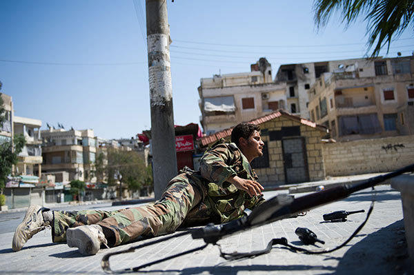 A rebel crawls to a reconnaissance position on the edge of the Salaheddin district of the restive northern city of Aleppo on August 10, 2012. The Free Syrian Army (FSA) continued to fight in Salaheddin following a major offensive by the Syrian government army on the key district which began two days ago.