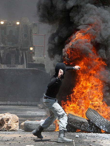 A Palestinian protester throws stones at Israeli soldiers, next to a pile of burning tyres, during a demonstration against the expropriation of Palestinian land by Israel in the village of Kafr Qaddum, near the West Bank city of Nablus, on August 10, 2012.