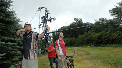 Joe Pitt of Windsor, Va., takes aim with his Hoyt Vantage Elite Plus bow while Jeremy Travis of Shinnston, W.Va., and Jacob Van Der Volgen of Erie wait their turns Friday at the 2012 International Bowhunting Organization's World Championships at Seven Springs Mountain Resort.