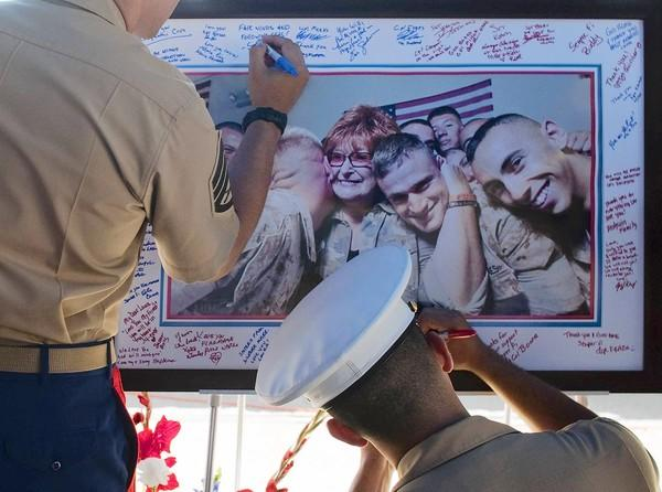 Marines write condolence messages on a photograph of Laura Froehlich at Riverside National Cemetery. Her warm smiles and hugs were welcomed by troops returning from battle and those heading to the war zone.
