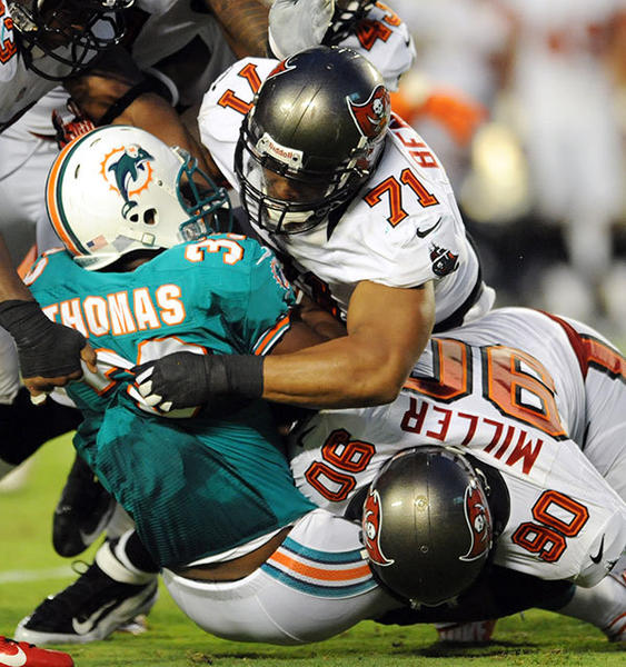 Daniel Thomas gets stopped by Michael Bennett (top ) and Roy Miller in the first quarter. Miami Dolphins vs. Tampa Bay Buccaneers, Sun Life Stadium.