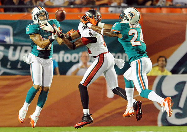 Tiquan Underwood of the Buccaneers catches a pass in between Jimmy Wilson (#27) and Sean Smith (#24) in the first quarter to set Tampa Bay up at the Dolphins' three yard line. Miami Dolphins vs. Tampa Bay Buccaneers, Sun Life Stadium.