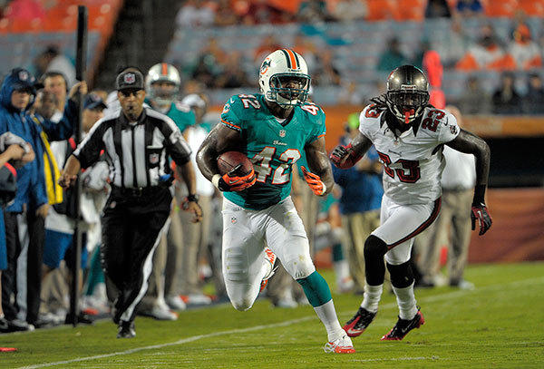 Miami Dolphins tight end Charles Clay catches a pass in front of Tampa Bay Buccaneers cornerback Mark Barron, during the second quarter of their preseason game, Friday, August 10, 2012, at Sun Life Stadium.