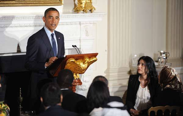 President Barack Obama speaks as Huma Abedin (R), the Muslim wife of disgraced Rep. Anthony Weiner, and who works as a top aide to Secretary of State Hillary Clinton, listens at an Iftar dinner celebrating Ramadan in the State Dining Room of the White House.